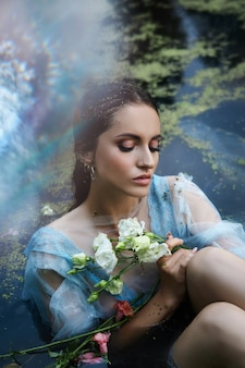 Art beautiful romantic woman lies in swamp in blue long dress with flowers. portrait brunette in transparent dress in water swamp mud duckweed. book cover