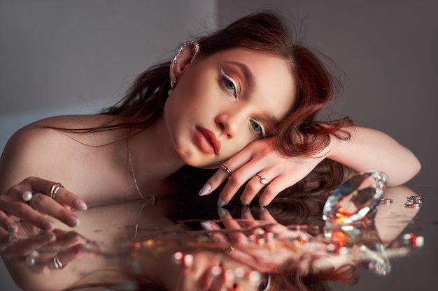 Art beautiful woman with creative makeup is lying on the mirror. beauty portrait of a romantic woman with jewelry