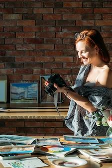 アートブログ。スタジオワークスペース。水彩画のアートワークの写真を撮る笑顔の女性画家