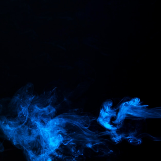 Art of bright blue smoke on black background with copy space