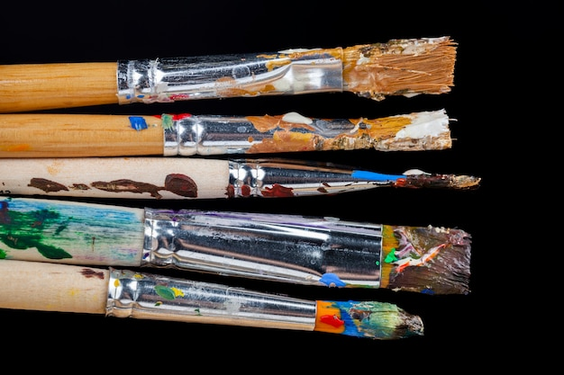 Art brushes smeared in paints of different colors after drawing pictures