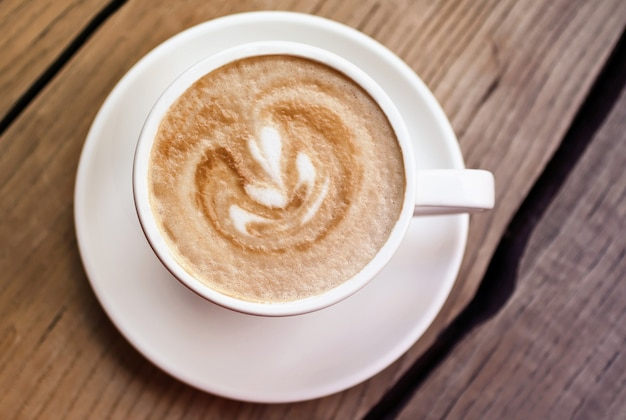 木の表面の白いカップにアートカプチーノ。上面写真。ミニマリズムの美しさ。温かみのある色調の写真。