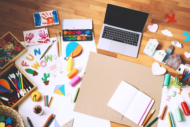 ノートパソコンの空の紙と創造的なものを作るための供給とアートの子フレーム