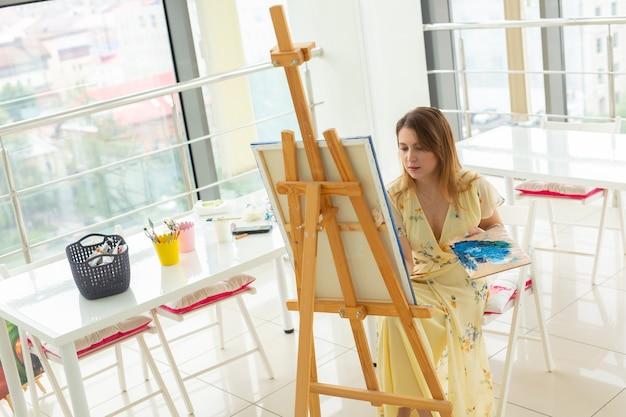 미술 수업과 드로잉 개념-스튜디오에서 그림을 작업하는 여자 아티스트.