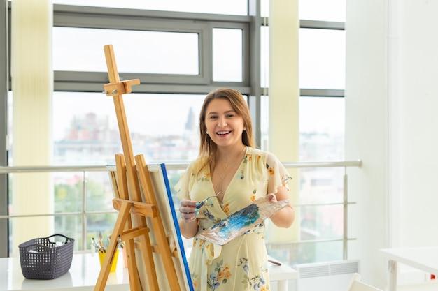 미술 수업, 그림, 창의성 개념 - 팔레트와 붓으로 이젤 앞에 앉아 있는 여학생.