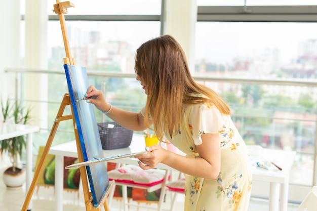 アートクラス、描画、創造性の概念-パレットでイーゼルの前に座っている女子学生