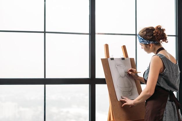 アートクラス。スタジオで花瓶のスケッチを描く若い女性の側面図