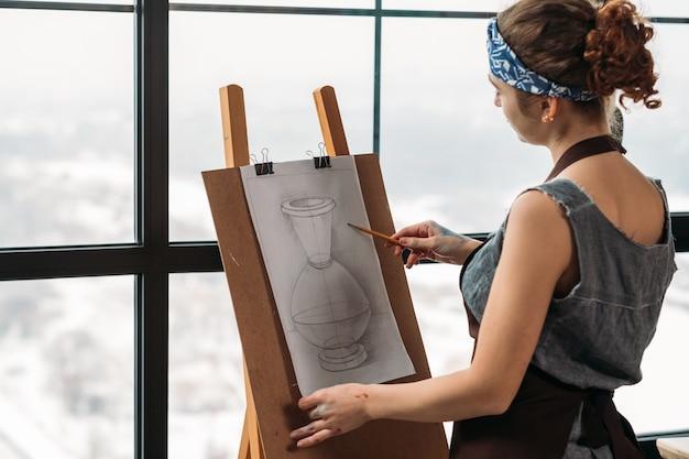 アートクラス。花瓶のスケッチを描く若い女性の側面図