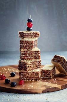 Художественная композиция из кусочков вафельного торта с шоколадным кремом и ягодами сверху. концепт для рекламы ресторанов и кафе.