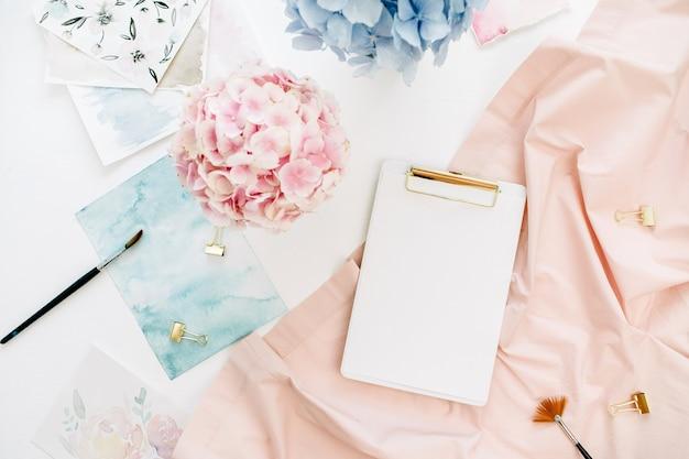 コピースペースクリップボード、パステルアジサイの花の花束、水彩画、桃色の毛布とアートコンポジションホームオフィスデスクワークスペース