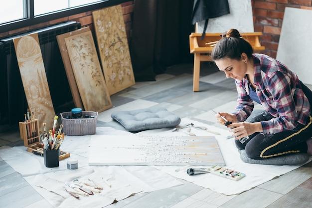 アートクラフトの趣味。レジャーとライフスタイル。床に織り目加工の絵を持つ女性。周りのアートワークと消耗品。