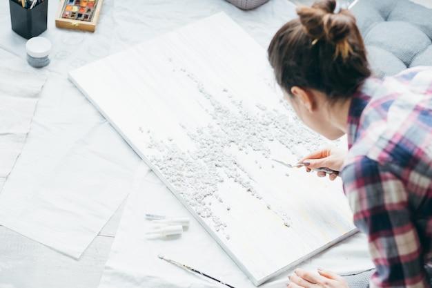 アートクラフトの趣味。レジャーとライフスタイル。床に織り目加工の絵を持つ女性。手元のモデリングツール。