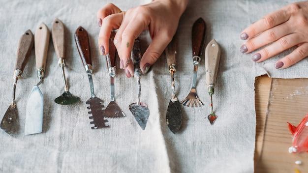 テキスタイルにアレンジされたアートクラフトセット。スカルプティングおよびモデリングツール。パレットナイフを選ぶ女性の手。