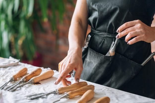 テーブルの上に配置されたアートクラフトツールセット。彫刻およびモデリング機器。ノミを選ぶ女性の手。
