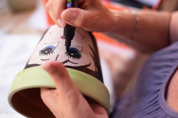 Искусство, творчество и люди концепции - крупным планом художница рисует и рисует цветочный горшок