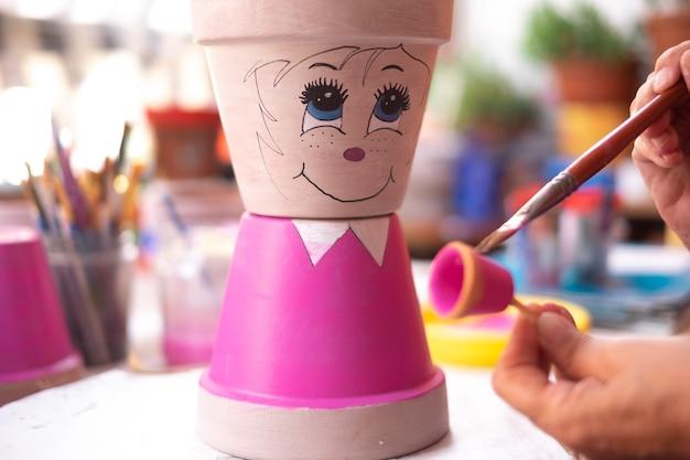 Искусство, творчество и люди концепции - крупный план художницы, рисующей цветочный горшок в студии