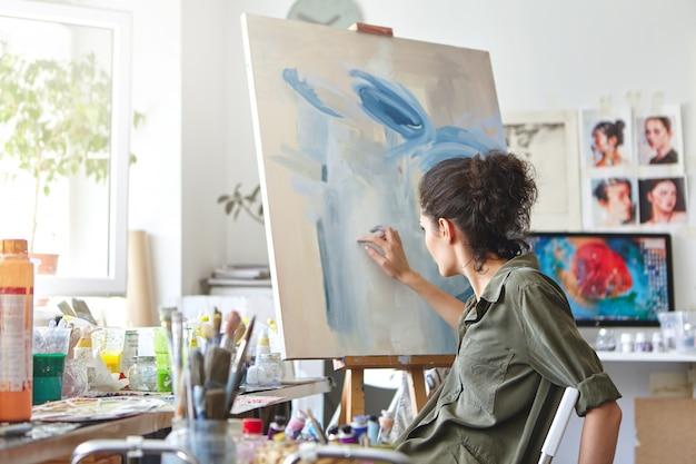 예술, 창의성, 취미, 직업 및 창조적 직업 개념. 흰색과 파란색 오일이나 아크릴 페인트를 사용하여 손가락으로 그림 이젤 앞에 의자에 앉아 바쁜 여성 아티스트의 후면보기
