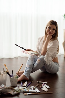 Art, creativity, hobby, job and creative occupation concept. female artist posing in front of window and painting with oil or acrylic paint