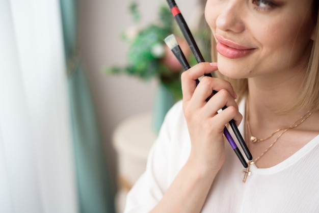 芸術、創造性、仕事そして創造的な職業の概念。女性アーティストが窓の前でポーズをとって油やアクリル絵の具で絵を描く
