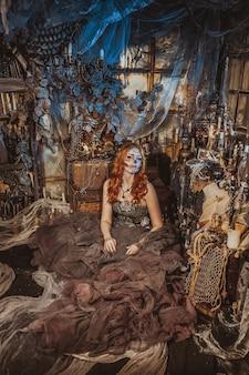 Искусство моды. красивая молодая женщина в элегантном историческом платье и с прической в стиле барокко, сидя в студии интерьера