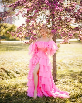 Art fashion portrait of a beautiful young blonde woman in a spring pink blooming garden in a long pink dress like a princess in fairytale