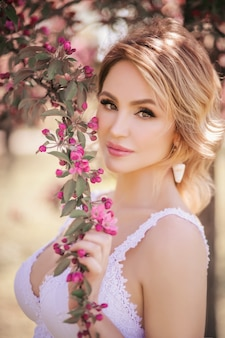 Art fashion portrait of a beautiful young blonde woman in a spring pink blooming garden in a white dress like a princess in fairytale