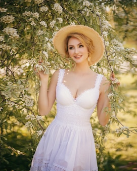 Art fashion portrait of a beautiful young blonde woman in a summer green blooming garden in a white light dress, in a straw hat. girl in country style