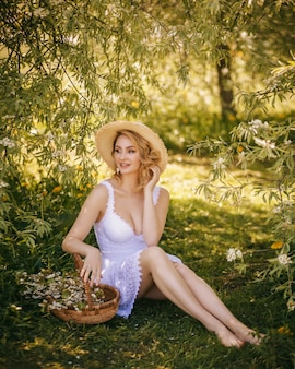 Art fashion portrait of a beautiful young blonde woman in a summer green blooming garden in a white light dress, in a straw hat and with a straw pottle. girl in country style