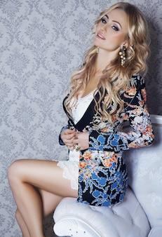 Арт-портрет молодой красивой блондинки сексуальной бизнес-леди с макияжем и прической в белом платье и цветочной куртке, сидя на диване