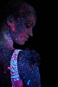 紫外光のアートガールコスモス。女性はヨガ、体のウォームアップをします。全身が色の droplet dropletで覆われている。アストラルヨガ。ノイズ、ピンぼけ