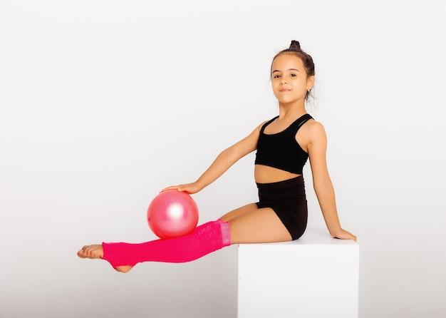 体操。柔軟な少女は、白い背景の上のボールで実行します。