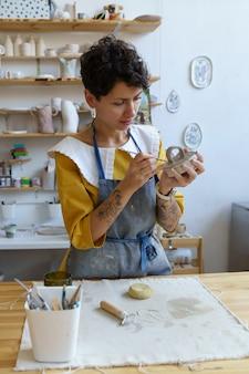 예술 취미와 비즈니스 젊은 여성은 도자기 스튜디오에서 도자기 항아리를 성형하는 데 집중하는 앞치마를 입습니다.