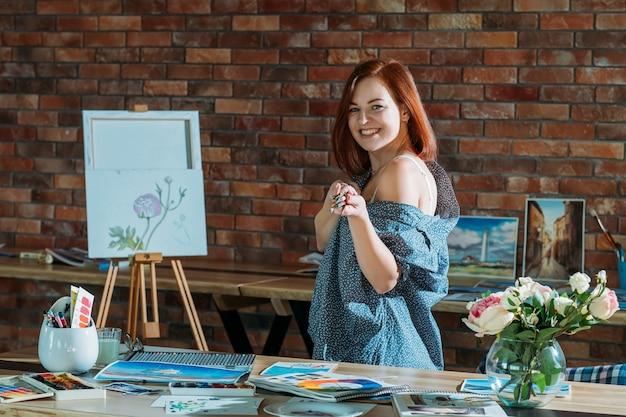 アート趣味。スタジオワークスペースの雰囲気。絵筆とイーゼルでポーズをとって赤毛の女性の笑顔