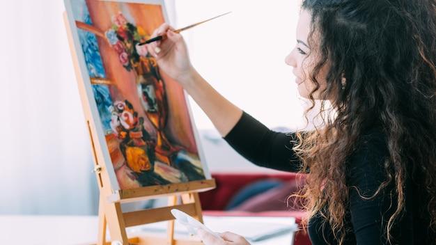 Художественное хобби. талантливая женщина, наслаждающаяся работой над натюрмортами в домашней студии.