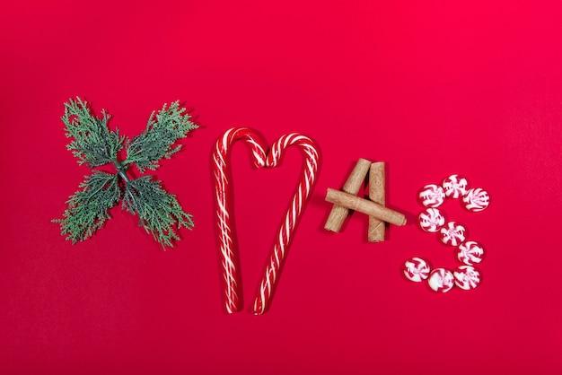 아트 레터링 크리스마스 트리, 사탕, 계피 젓가락은 빨간색 배경에 있습니다. 크리스마스 컨셉
