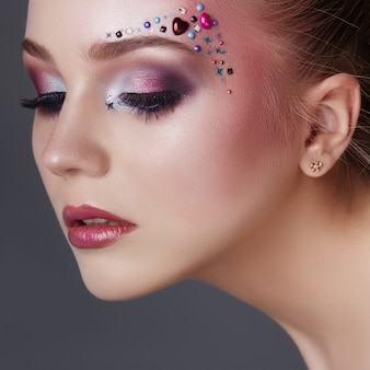 Art makeup over eyebrows of women many rhinestones