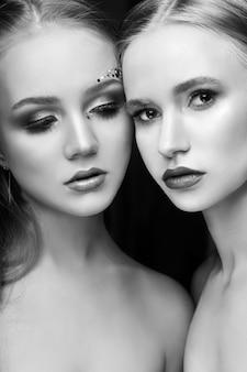 Художественный макияж двух женских объятий, множество стразов различной формы, красивое лицо, уход за гладкой кожей. красота макияж на лице двух женщин крупным планом. профессиональный визажист, длинные красивые волосы
