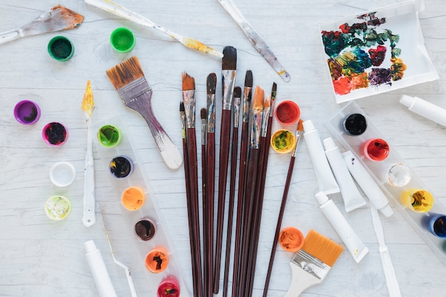 Art materials scattered on white table from above
