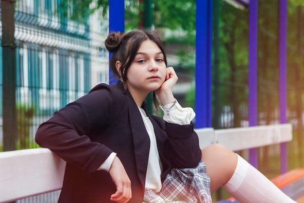 アートノイズフィルムスタイルの画像。学校で白いブラウス、格子縞のスカートとジャケットの13歳の女子高生の肖像画。カメラを見てポーズをとる感情的な十代の少女。学齢期と学習の概念