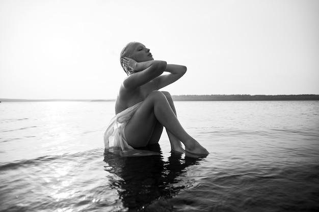 짧은 머리를 가진 예술 누드 섹시한 금발은 해질녘 호수의 해안 해변에 물에 앉아 있습니다. 젖은 머리와 여성의 몸. 한적한 해변 휴가. 검정색과 흰색