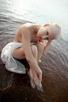 짧은 머리를 가진 예술 누드 섹시한 금발은 해질녘 호수의 해안 해변에 물에 앉아 있습니다. 젖은 머리와 여성의 몸. 한적한 해변 휴가