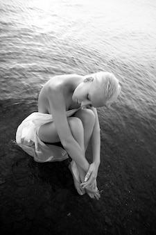 Art nude sexy blonde with short haircut is sitting in water on shore beach of lake at sunset. wet hair and a woman body. secluded beach holiday. black and white