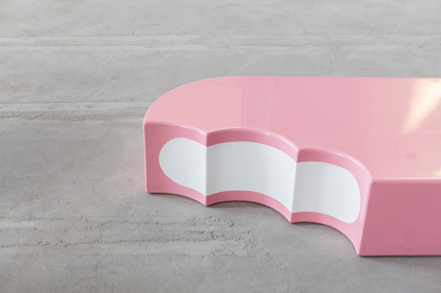 Art object - bench in the form of pink ice cream, standing on the concrete floor
