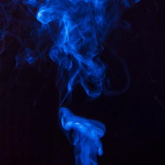 Искусство ярко-голубого дыма движется вверх на черном фоне