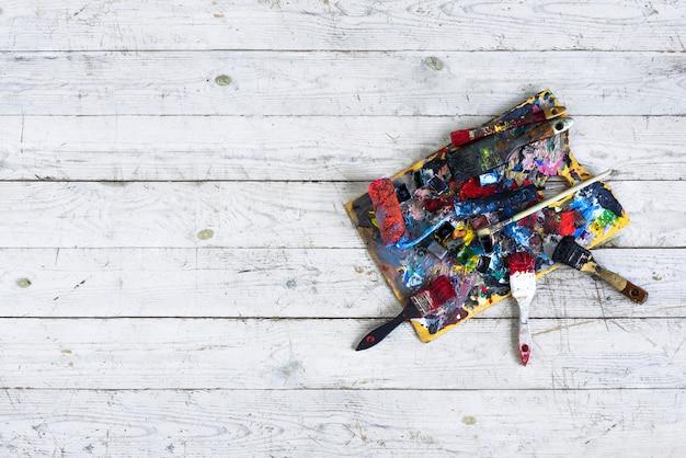 Художественная палитра для красок с кистями, изолированными на деревянном.