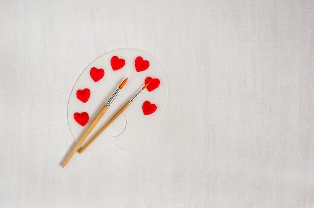 Художественная палитра с красными сердцами и кисти на белом фоне деревянные.