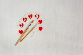 Художественная палитра с красными сердцами, буквы любви и кисти на белом фоне деревянные.