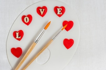 赤いハート、愛の手紙、白い木製の背景上のブラシでアートパレット。