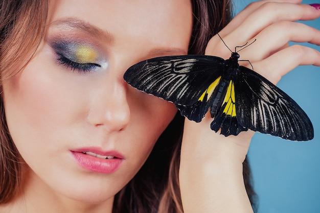 아트 포토 패션 모델은 밝은 메이크업을 보여줍니다. 아름 다운 젊은 섹시 한 여자 녹색 눈과 라이브 나비 노란색 검은 날개. 관능적인 클로즈업 초상화 완벽 한 피부, 전문 메이크업 및 헤어스타일