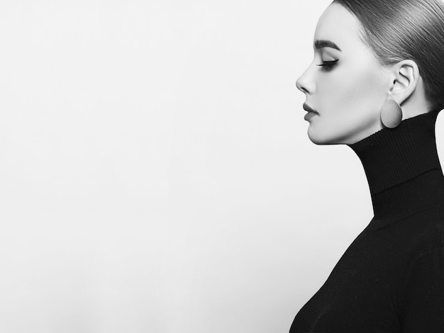 Art portrait of a beautiful, elegant woman in a black turtleneck and gold jewelry